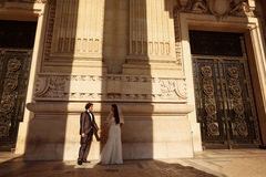Bride and groom in front of a big building Stock Photos