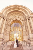 Bride and groom in front of a big building Royalty Free Stock Photos