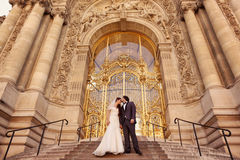 Bride and groom in front of a big building Stock Photography