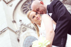 Bride and groom in front of the church Stock Photos