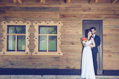 Bride and groom in front of house golding togher Royalty Free Stock Photo