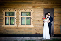 Bride and groom in front of house holding togher Stock Image