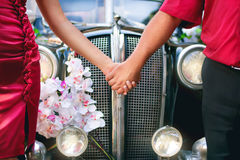 Bride and groom in front of a retro car stock images