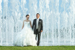 Bride and groom in front of water fountain Stock Photography