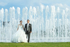 Bride and groom in front of water spray fountain Royalty Free Stock Photography