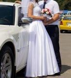 Bride and groom in front of wedding car. Bride and groom standing in front of wedding car Stock Photography