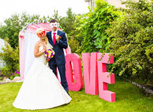 Bride and groom with funny carnival masks Royalty Free Stock Photography