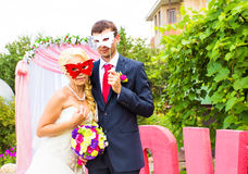 Bride and groom with funny carnival masks Royalty Free Stock Photos