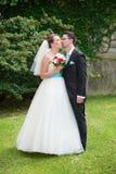 Bride and groom in a garden Stock Photos