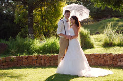 Bride and groom in garden wedding with parasol Stock Photos