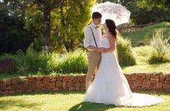 Bride and groom in garden wedding with parasol royalty free stock photos