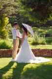 Bride and groom in garden wedding with parasol Royalty Free Stock Image