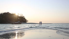 Bride and groom get across shallow water to island stock footage