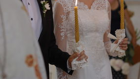 Bride and groom get married in church. They keep church candles in their arms stock footage