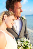 Bride And Groom Getting Married In Beach Ceremony. Looking Out To Sea Stock Photography