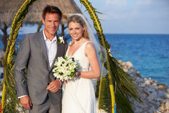 Bride And Groom Getting Married In Beach Ceremony. Smiling To Camera Stock Photography