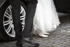 Bride and groom getting out of the car Royalty Free Stock Images
