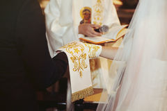 Bride and groom giving vows at wedding ceremony, hands closeup Stock Image