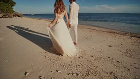 The bride and groom go barefoot on a sandy beach next to the blue ocean. They are holding hands. Happy together stock footage