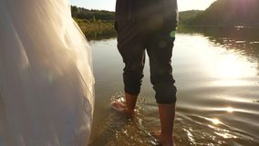 The bride and groom go barefoot on the water on the river bank. Close-up. couple in love walk on the beach hand in hand stock video footage