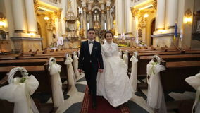 Bride and groom go out of the church stock video footage