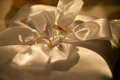 Wedding rings on satin pillow with ribbon royalty free stock photos