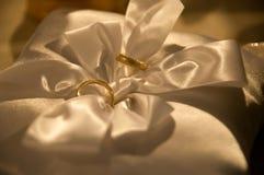 Wedding rings on satin pillow with ribbon royalty free stock photos