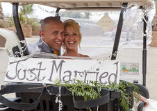 Bride and Groom in a golf cart Royalty Free Stock Images