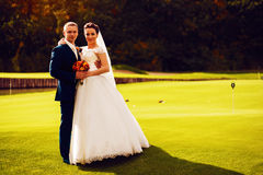 Bride and groom on golf field Stock Photography