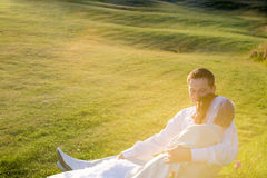 Bride and groom on the grass looking at sunset Stock Photo