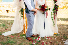 Bride and groom on the grass under the arch at the wedding cerem Stock Images