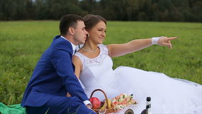 Bride and groom on a green meadow in summer day. The bride and groom are sitting on a green field, meadow and enjoy each other.Picnic newlyweds on green field stock video footage