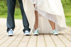 Bride and groom. Bride and grom's legs in color gym shoes Royalty Free Stock Images