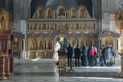 Bride and groom and guests stand opposite the iconostasis. MOSCOW - MARCH 10: bride and groom and guests stand opposite the iconostasis during orthodox wedding Stock Photography