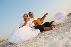 Bride and groom with the guitar. Bride and groom playing at the guitar on the beach Royalty Free Stock Photos