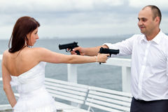 Bride and groom with guns Stock Photos