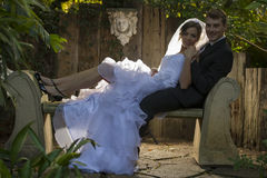 Bride and groom with hairlight sitting on a concre Royalty Free Stock Photography