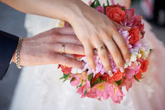 Bride and groom hand with rings on wedding bouquet Royalty Free Stock Photography