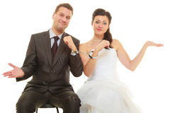 Bride and groom in handcuffs wearing wedding outfits. Couple problems, love forever concept. Bride and groom in handcuffs wearing wedding outfits Royalty Free Stock Images