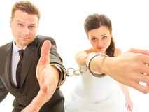 Bride and groom in handcuffs wearing wedding outfits Stock Photo