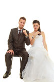Bride and groom in handcuffs wearing wedding outfits. Couple problems, love forever concept. Bride and groom in handcuffs wearing wedding outfits Stock Image