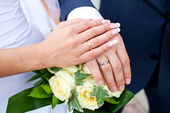 Bride and groom hands on bouquet of flowers Stock Images