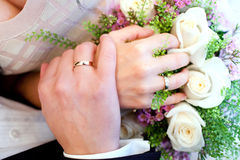 Bride and groom hands and bride's bouquet. Bride and groom hands with engagement rings and wedding bouquet Stock Photo