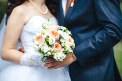 Bride and groom hands holding wedding bouquet. Marriage concept. Bouquet between the bride and groom, close-up Royalty Free Stock Photo