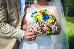 Bride and groom hands holding wedding bouquet. Marriage concept. Bouquet between the bride and groom, close-up Stock Image