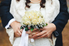Bride and groom hands holding wedding bouquet. Marriage concept. Bouquet between the bride and groom, close-up Stock Photography