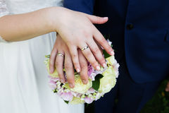 Bride and groom hands with rings and bridal bouquet Stock Photography