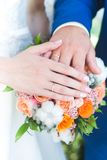 Bride and groom Hands and rings on wedding bouquet Stock Photography