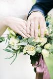 Bride and groom Hands and rings on wedding bouquet Royalty Free Stock Photos