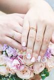 Bride and groom Hands and rings on wedding bouquet Royalty Free Stock Image